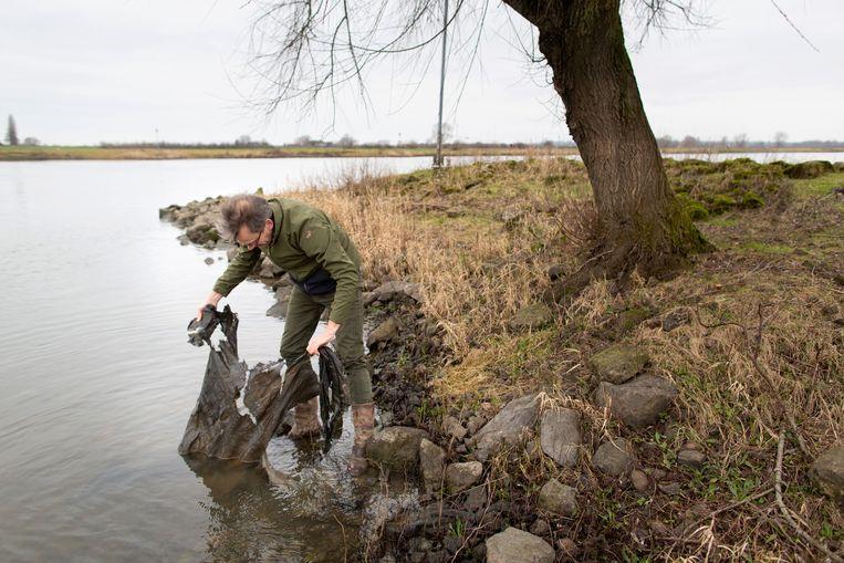 Wim Eikelboom langs de IJssel bij Zwolle, waar hij overal dit soort geotextiel vindt.  Beeld Herman Engbers