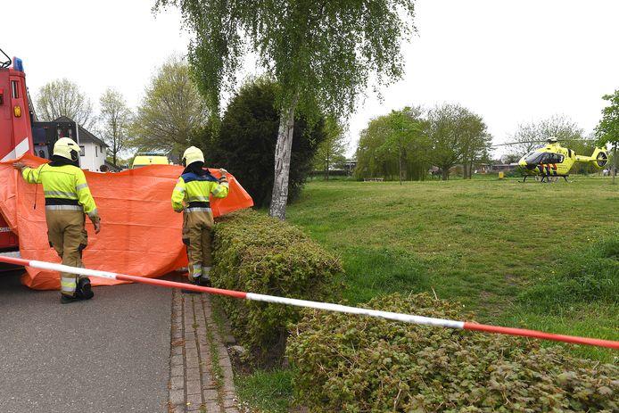 Brandweer verleent assistentie kort na het ongeval op de Merel in Boxmeer, waar een jongetje van vier jaar ernstig gewond raakte aan zijn hoofd. Op de voorgrond de opening in de heg waardoor het kind vermoedelijk de straat op is gelopen.