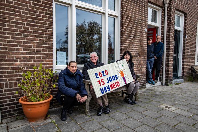 (Vlnr) Rosalie en moeder Kitty Winkelman (behoren tot één coronabubbel) tonen met Rietje Oosterbroek het kunstwerk. Dat staat bij Rob Smolders en Saskia de Rijk aan de Diepenveenseweg voor het raam en toert de komende weken door Voorstad.