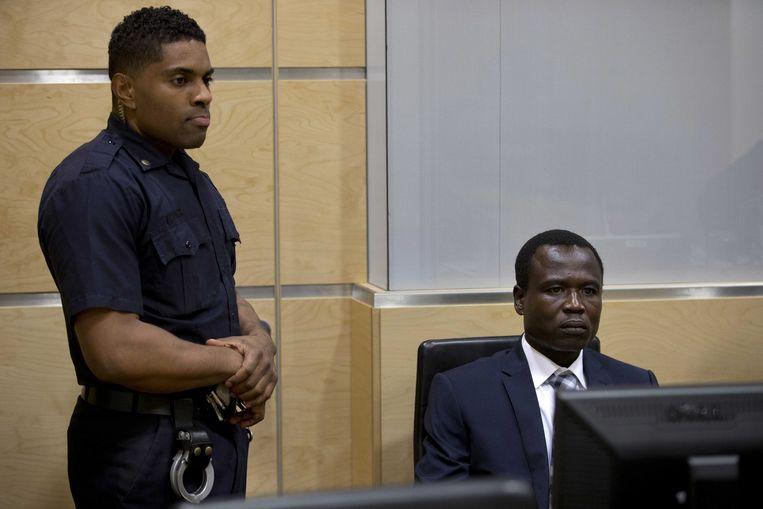 Dominic Ongwen (r) in de rechtszaal van het Internationaal Strafhof in Den Haag tijdens de behandeling van zijn zaak.  Beeld EPA