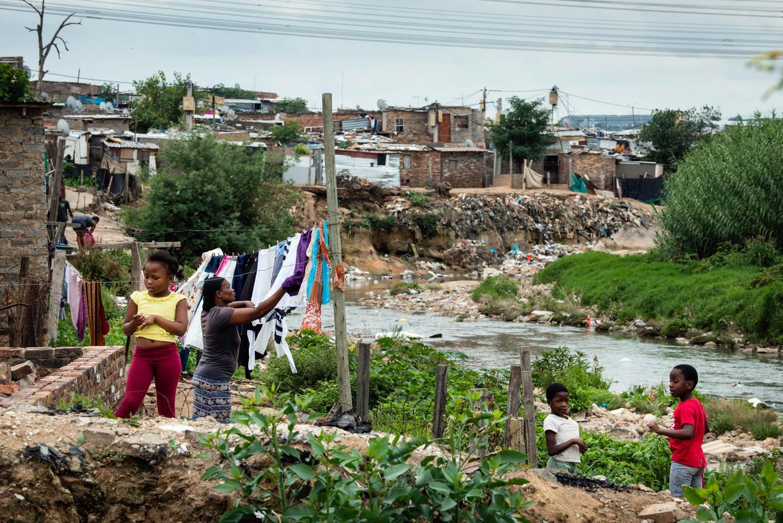 Een vrouw hangt haar was te drogen langs de oever van de vervuilde Juksei-rivier in Stwetia, een van de armste plekken in Johannesburg.