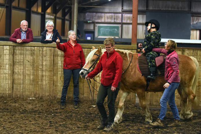 Bij Manege De Belle in Etten-Leur rijden mensen met een beperking paard onder leiding van Jet van Dam (staand, midden).