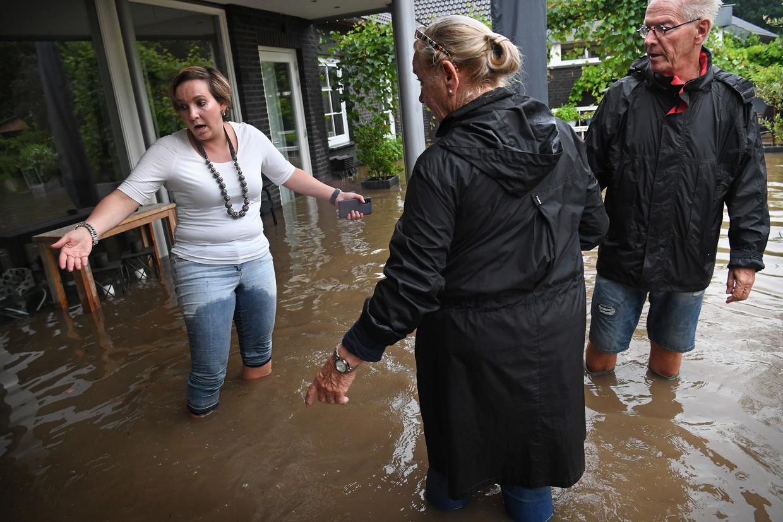 Een vrouw in Mechelen ziet vol ontzetting hoe het water bezit heeft genomen van haar huis. Beeld Marcel van den Bergh / de Volkskrant