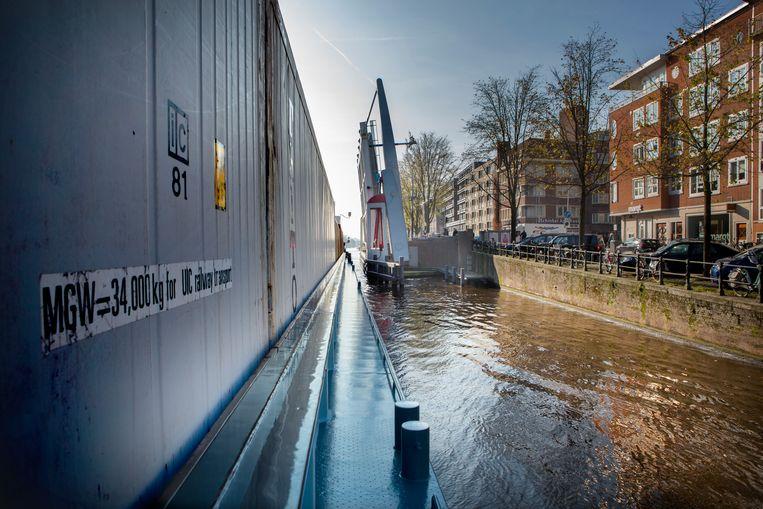Het containerschip past net langs de vele bruggen op de Amsterdamse grachten.  Beeld Maarten Hartman