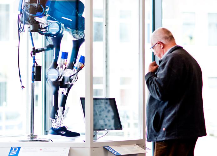 Een bezoeker van het Stadskantoor bekijkt het exoskelet in de publiekshal aandachtig.