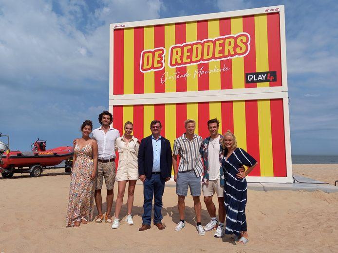 De cast van 'De Redders', met onder andere Joni Ceusters en Julie Vermeire, samen met burgemeester Bart Tommelein bij de redderspost in Oostende.