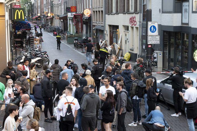 Politie en publiek in de Lange Leidsedwarsstraat in Amsterdam. Bij een schietpartij is misdaadverslaggever Peter R. de Vries zwaargewond geraakt.