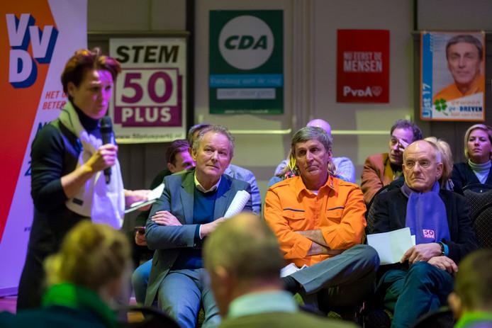 Politiek debat in Rosmalen met Hanneke Welten (VVD) aan de microfoon en (zittend van links naar rechts) Paul Kagie van Leefbaar 's-Hertogenbosch, Sjef van Creij van gewoon ge-DREVEN en Hans Krosse van 50PLUS.