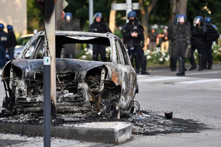 Een uitgebrande auto in de wijk Les Grésilles in Dijon.  Beeld AFP