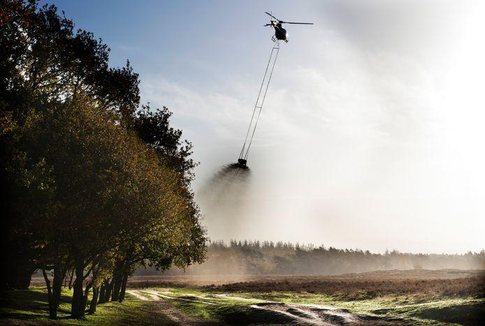 Een helikopter strooit kalk uit boven natuurgebied De Ginkel bij Ede. Door de hoge concentraties stikstof verzuurt de bodem en krijgen vogels zwakkere botten. Door kalk uit de strooien wordt de bodem minder zuur.