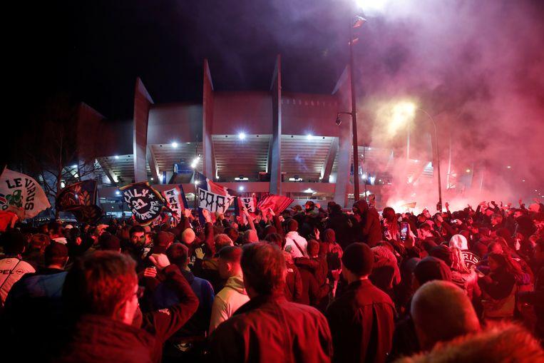 Fans van PSG verzamelen buiten het stadium omdat ze binnen niet toegelaten zijn voor de Champions League-match tegen Dortmund, half maart. Beeld REUTERS
