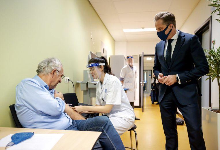 Een medewerker dient een vaccin tegen tuberculose toe, tijdens een bezoek van minister Hugo de Jonge. Beeld ANP