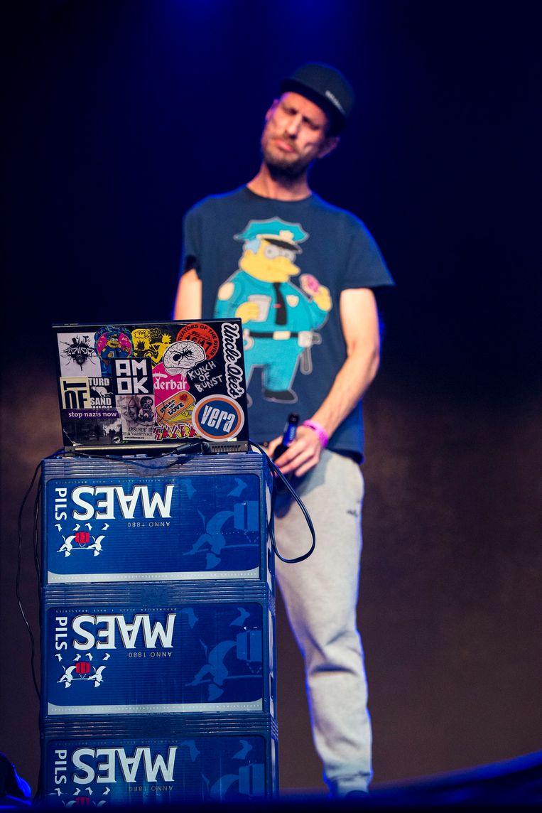 Andrew Fearn, in een T-shirt van Chief Wiggum, de dikke flik uit The Simpsons, en een beats brakende laptop bovenop drie bierbakken. Beeld Koen Keppens