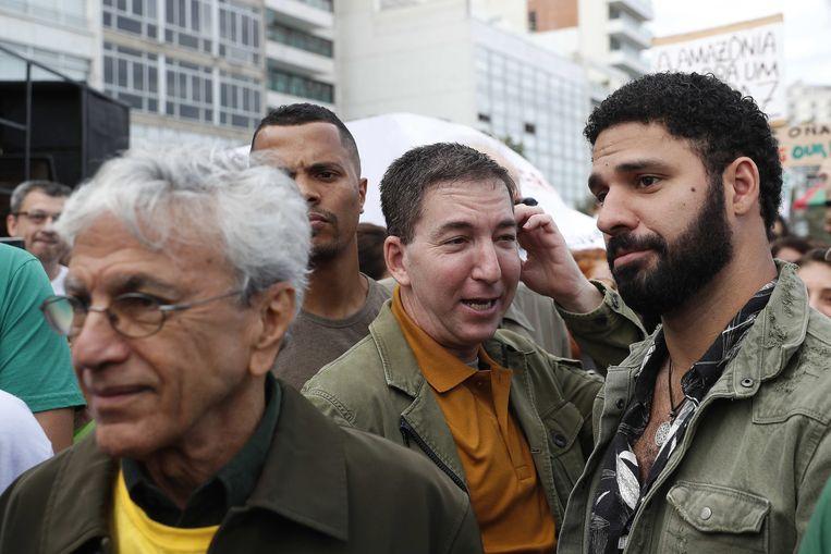 Glenn Greenwald met echtgenoot David Miranda (r) tijdens een protestmars tegen de vernietiging van het Amazone regenwoud, in augustus. Beeld EPA