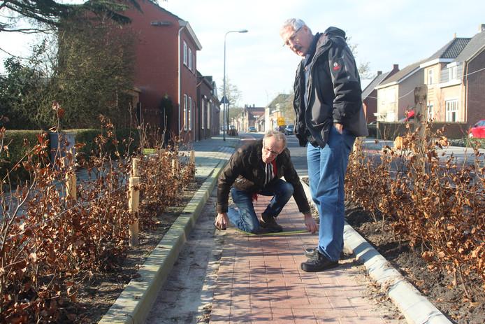 Piet Brosens en Nico Geers van de Fietsersbond meten de niveauverschillen in de Sint Janstraat. archieffoto BN DeStem