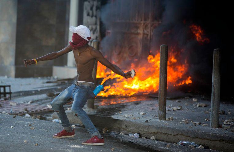 Een demonstrant gooit een steen naar de politie in Port-au-Prince in Haïti. Beeld AP
