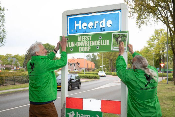 Heerde mag zich het meest zwijn-onvriendelijke dorp van de Veluwe noemen. Harry Voss (l.) van de Faunabescherming Gelderland plakt het bord op.