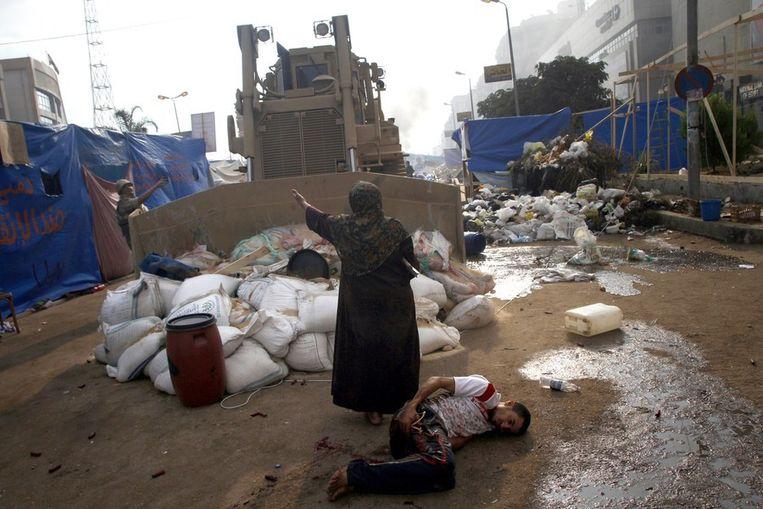 Een vrouw probeert te verhinderen dat een bulldozer een gewonde jongeman overrijdt, gisteren in Caïro. Beeld afp