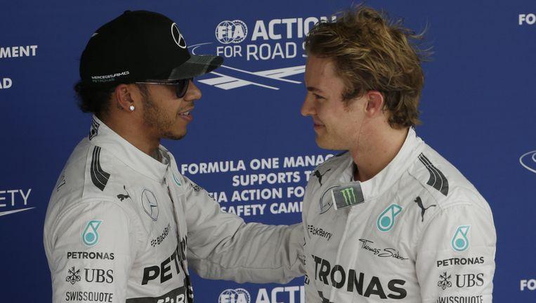 Rosberg (R) ontvangt felicitaties van Hamilton. Beeld AP