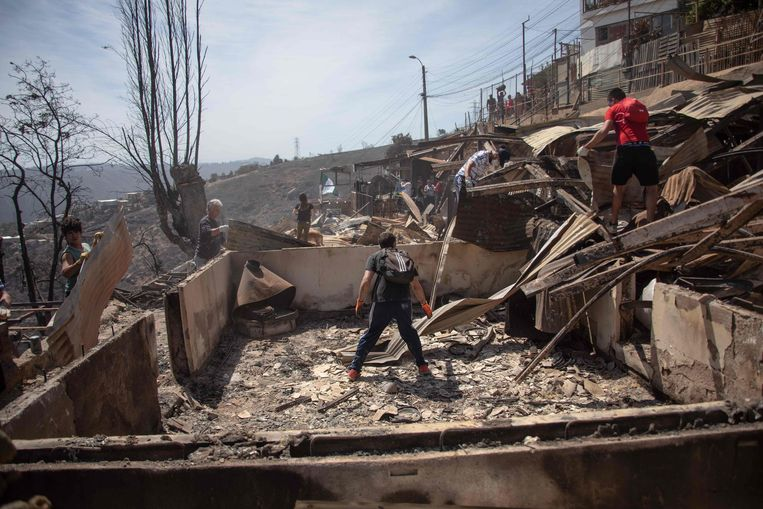 Mensen zoeken tussen de verbrande huizen of er nog iets van hun bezittingen te redden valt.