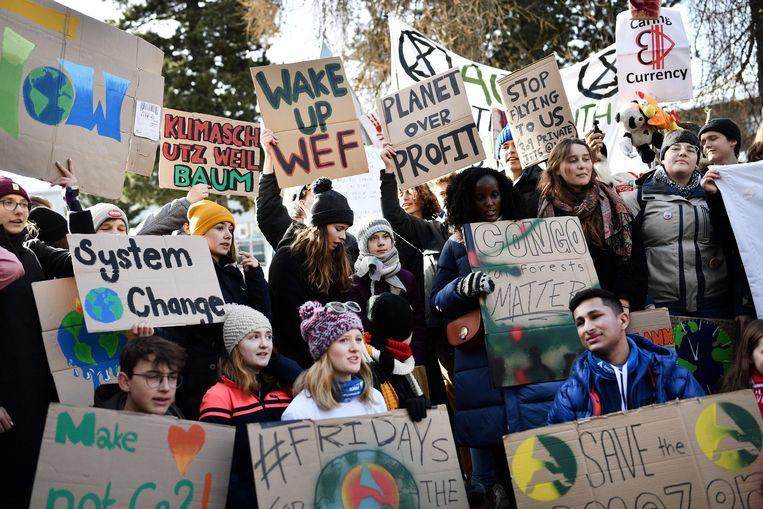 Greta Thunberg, pal in het midden, loopt mee in een klimaatmars in de straten van Davos, januari dit jaar. Beeld AFP