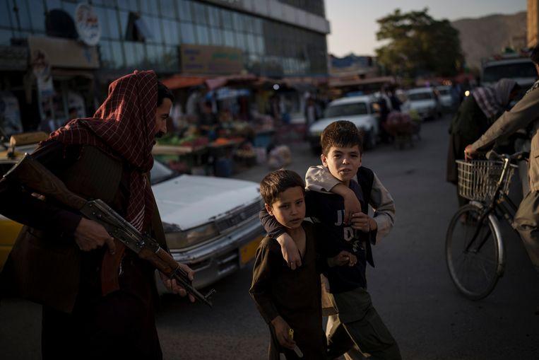 Archiefbeeld 14 september 2021: Afghaanse jongens wandelen voorbij een talibanstrijder in Kaboel.  Beeld AP