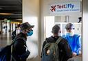 Reizigers doen een coronatest voordat zij gaan vliegen vanaf Schiphol.  De luchthaven was in juli de drukste van Europa.