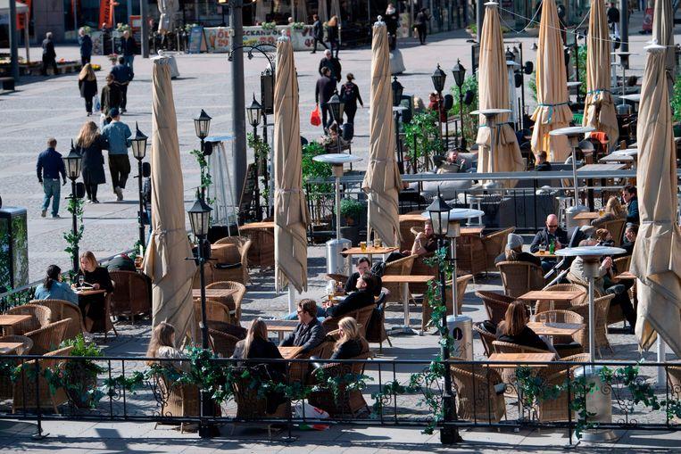 Mensen op het terras in Zweden. In het land gelden minder strenge lockdownregels dan in de rest van Europa. Beeld AFP