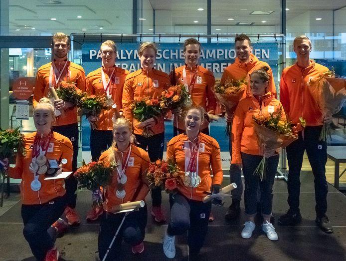 Bloemen en onderscheidingen voor de zwemploeg en enkele assistenten.