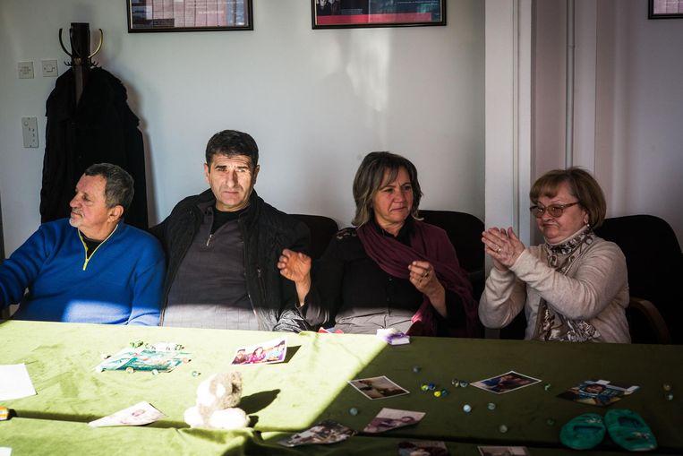 Nabestaanden klappen in Sarajevo bij het horen van het vonnis. Op tafel liggen foto's van omgekomen familieleden. Beeld Nicola Zolin