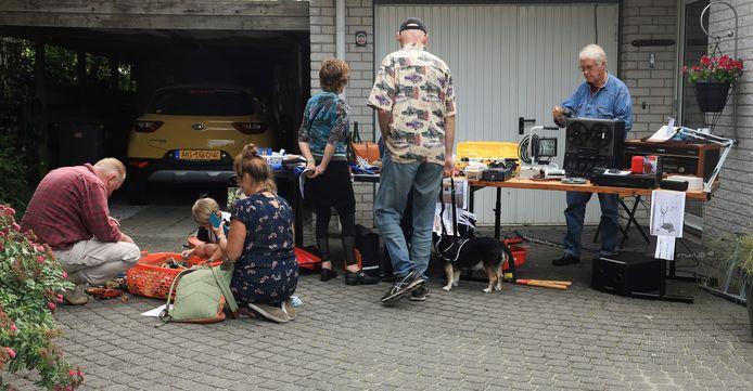 Bezoekers van de garagesale zoeken naar koopjes.