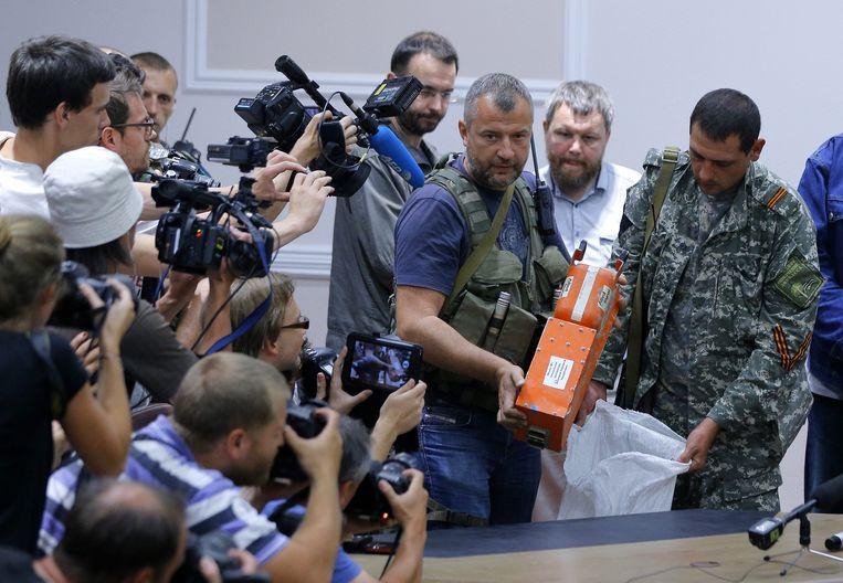 2014-07-22 02:16:54 DONETSK - Pro-Russische rebellen in Oekraïne dragen de zwarte dozen van het rampvliegtuig MH17 van Malaysia Airlines over aan een Maleisische delegatie.  In de zwarte dozen worden de vluchtgegevens en de gesprekken in de cockpit opgeslagen. EPA/ROBERT GHEMENT Beeld EPA