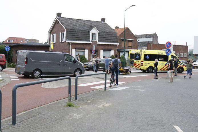 De fietser krijgt eerste hulp na de aanrijding door een bestelbus op de rotonde in Boxmeer.
