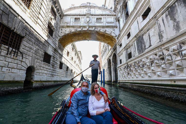 Een koppel geniet van een uitstap in een gondel op de Venetiaanse kanalen aan de Ponte dei Sospiri.  Beeld AFP