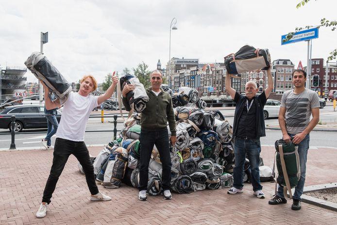 Medewerkers Sheltersuit delen pakken uit in Amsterdam.