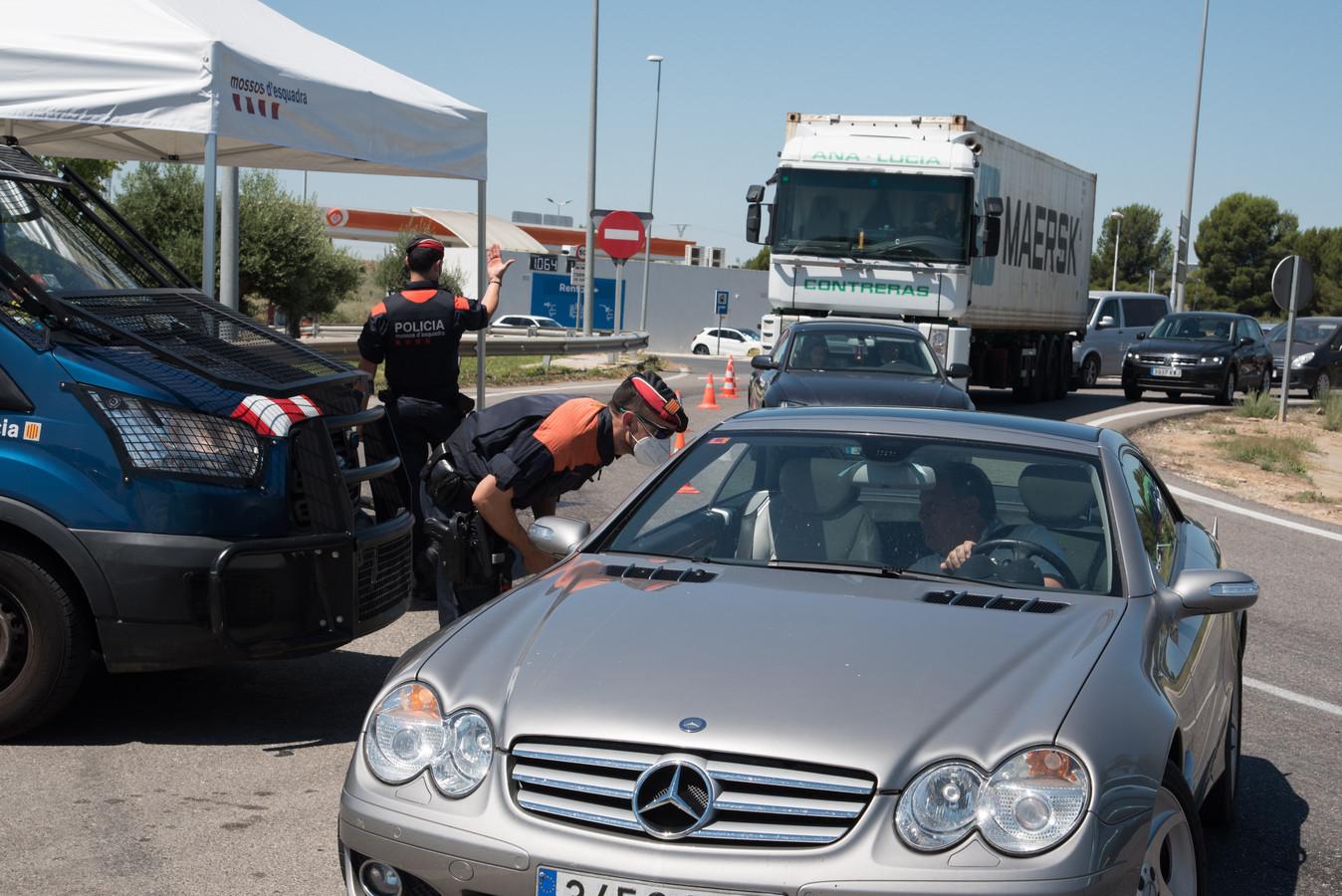 Verkeerscontrole in de Spaanse regio Catalonië. Door de toename van het aantal coronabesmettingen zullen er minder toeristen op de weg zijn.