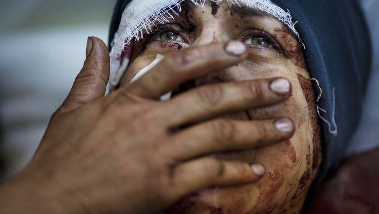 Een vrouw die zwaar gewond is geraakt huilt. Haar man en twee van haar kinderen zijn overleden bij de beschietingen op Idlib. Beeld ap