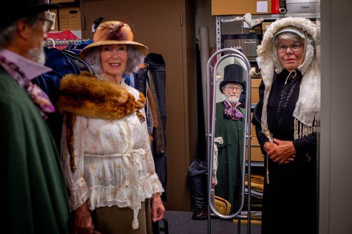De Werkgroep Maas en Waalse Streekdracht en Mode en Streekdracht moet verhuizen. Vlnr. Jan Stuart met Engelse mode van rond 1850, Wies Berris met  Europse mode van rond 1904 en Ger van Dreumel in streekdracht met muts en poffer.