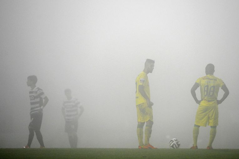 Pacos Ferreira and Sporting's players wait in the fog before the start of the second half-time during the Portuguese league football match FC Pacos de Ferreira vs Sporting CP at the Mata Real Stadium in Pacos Ferreira on April 5, 2014. Sporting won the match 3-1.     TOPSHOTS/AFP PHOTO/MIGUEL RIOPA Beeld AFP