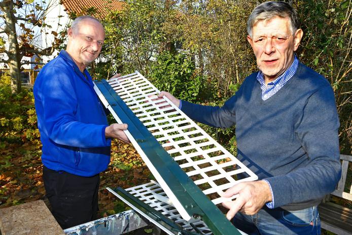 Wybo Vrijburg (l) en Theo Verhaar van de historische kring Oud-Alkemade met de wieken van de vernielde molen. Vrijburg gaat de molen weer opknappen.