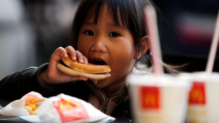 Een meisje eet een McDonald's-burger in Milaan. Beeld reuters