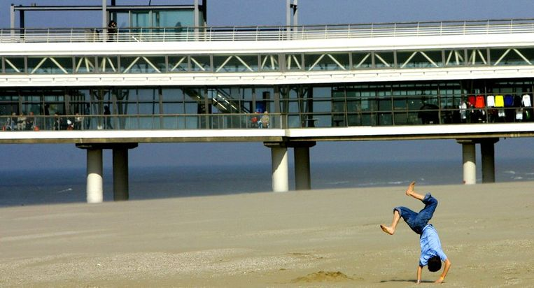Een kind speelt op het strand van Scheveningen, op de achtergrond de Pier, maart 2005. Beeld anp