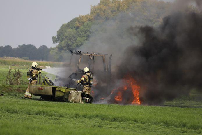 Brandweerlieden proberen het landbouwvoertuig te blussen.