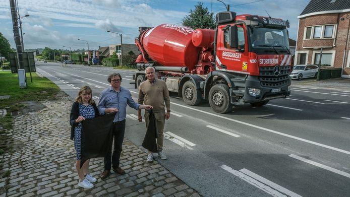 We zien op de foto buurtbewoners Caroline Lagache, Philip Van Bost en Edy De Decker, met enkele zwarte vlaggen. Achter hen passeert een betonwagen van Bosschaert, op 't Hoge (N50)