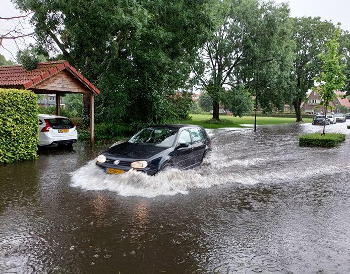 Een auto baant zich een weg door een ondergelopen straat in Doetinchem.