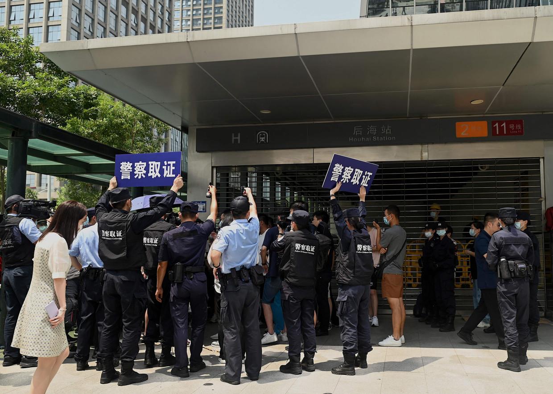 Aan het hoofdkwartier van Evergrande in het Chinese Shenzhen verzamelden zich deze week mensen die protesteerden tegen de gang van zaken bij het conglomeraat. Beeld AFP