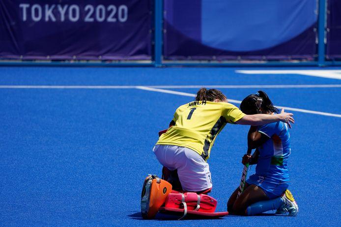 Claire Hinch, de keeper van de hockeysters van Groot-Brittannië, troost Neha Neha van India.