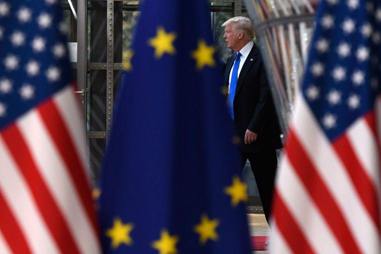 De Amerikaanse president Donald Trump loopt achter Amerikaanse en EU-vlaggen door. Beeld Photo News
