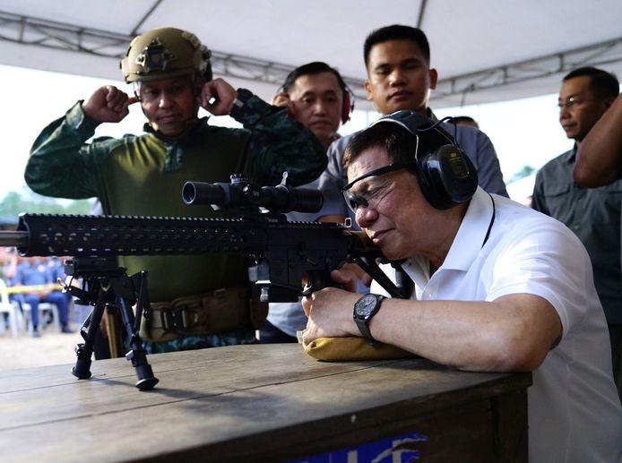 De Filipijnse president Rodrigo Duterte oefent met een machinegeweer tijdens een bezoek aan een militaire basis .
