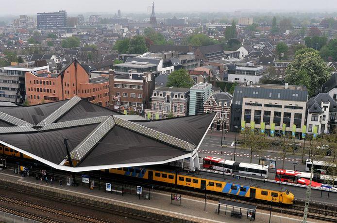 Station Tilburg vanuit de lucht, met veel bebouwing om het spoor.
